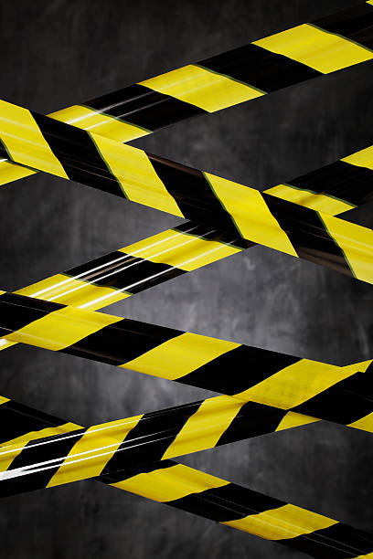Don't Go There! Black and yellow plastic barrier tape blocking the way. affix stock pictures, royalty-free photos & images