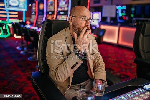 Senior men using slot machine to gamble in night club, having difficulties to make money, he is losing
