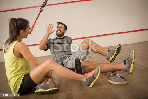 Playful friends having fun while resting on a squash court. Woman is about to hit her friend with a racket.