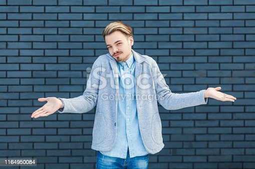 istock I don't know. Portrait of careless or confused handsome young blonde man in casual style standing with raised arms and looking at camera with doubtful face. 1164950084