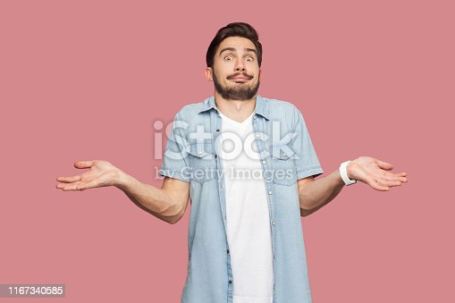 istock I don't know. Portrait of confused handsome bearded young man in blue casual style shirt standing with raised arms and looking at camera with answer. 1167340585