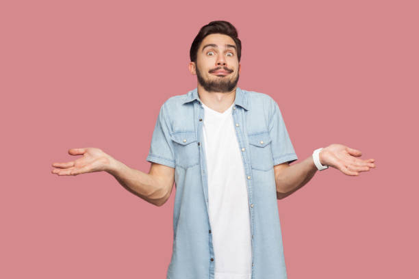 I don't know. Portrait of confused handsome bearded young man in blue casual style shirt standing with raised arms and looking at camera with answer. stock photo