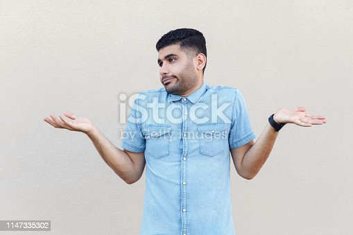 istock I don't know. Portrait of confused handsome young bearded man in blue shirt standing with raised arms and dont know what to do or choose. 1147335302