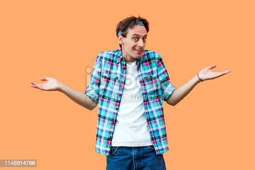 836798276 istock photo I don't know. Portrait of confused young man in casual blue checkered shirt headband standing raised arms and looking at camera with doubtful face 1145914766