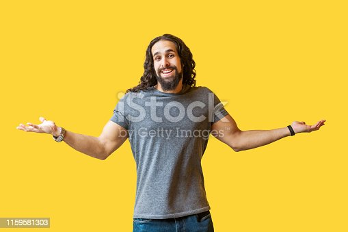 836798276 istock photo I don't know. Portrait of thinking bearded young man with long curly hair in grey tshirt standing with raised arms and looking at camera with confused face. 1159581303