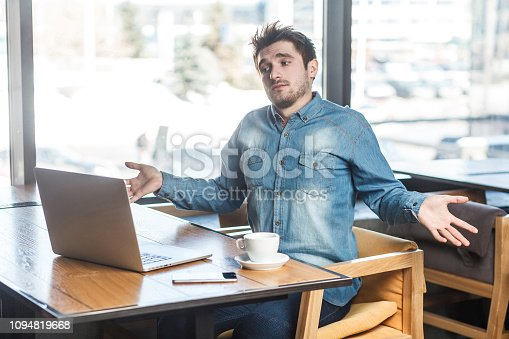 istock I don`t know! Side view portrait of confused handsome bearded young freelancer in blue jeans shirt are sitting in cafe and making video call on laptop with raised arms and puzzled face. 1094819668