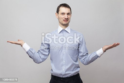 836798276 istock photo I don't know, which one to choose. Portrait of confused bristle businessman in blue shirt standing with raised arms and looking at camera. 1089490378