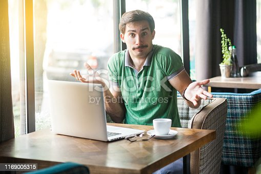 836798276 istock photo I don't know! Young confused businessman in green t-shirt sitting with laptop, looking at camera with raised arms and puzzled. 1169005315