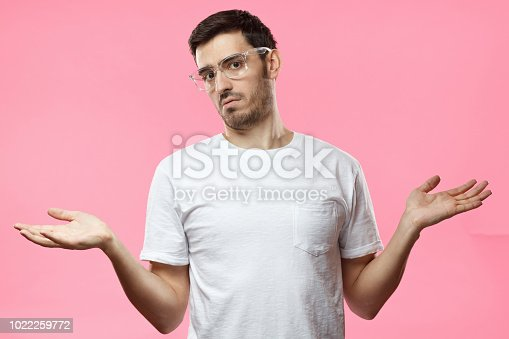 I don't know. Young man isolated on pink background being at a loss, showing helpless gesture with arm and hands, mouth curved as if he does not know what to do