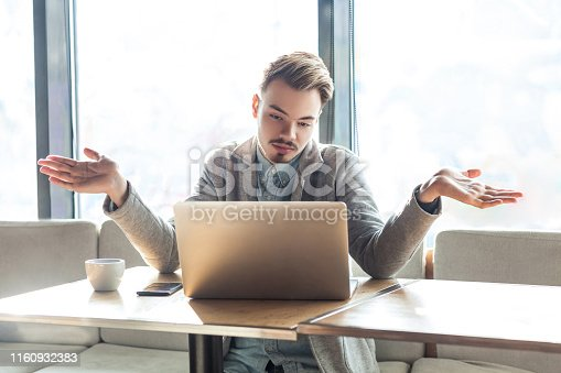 836798276 istock photo I don't know!Portrait of confused handsome bearded young freelancer in grey blazer are sitting in cafe and making video call on laptop with raised arms and puzzled face. 1160932383