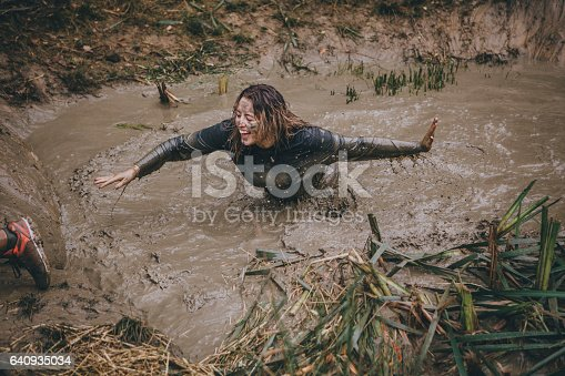 Woman is wading through a ditch full of muddy water as part of a charity obstacle course.