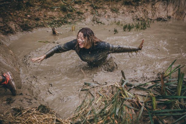 Don't Leave Me In! Woman is wading through a ditch full of muddy water as part of a charity obstacle course. mud run stock pictures, royalty-free photos & images