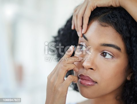 Cropped shot of a beautiful young woman putting in her contact lenses at home