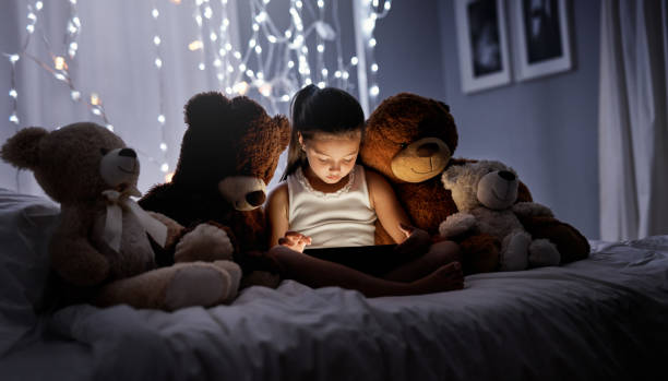Don't let late night screen-time become an unhealthy habit Shot of an adorable little girl using a digital tablet in bed at night teddy bear stock pictures, royalty-free photos & images