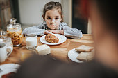 Small girl feeling sad because she doesn't like her breakfast at dining table.