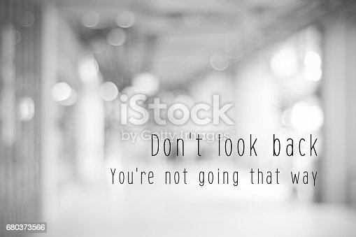Don't look back, you're not going that way, life quotation on blur abstract black and white bokeh light background