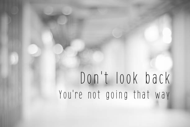 Don't look back, you're not going that way, life quotation on blur abstract black and white bokeh light background stock photo