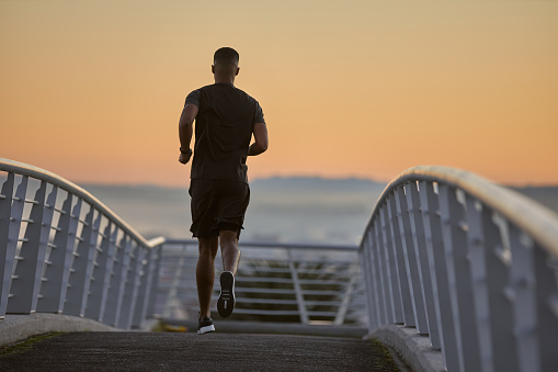Rearview shot of a sporty young man running on a bridge in the city