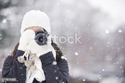 Shot of a young woman out in the snow with her camerahttp://195.154.178.81/DATA/i_collage/pu/shoots/806414.jpg