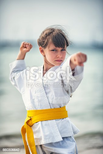 Little girl practicing karate on the beach.