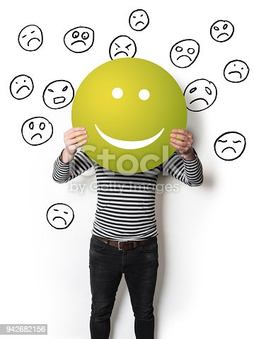 Man holding a green smiling emoticon in front of sad faces hand drawn on a white wall.