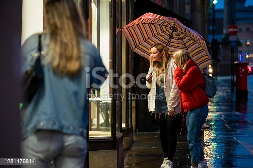 Two female students walking through the city centre on a rainy evening and looking in a shop window. They are holding an umbrella.