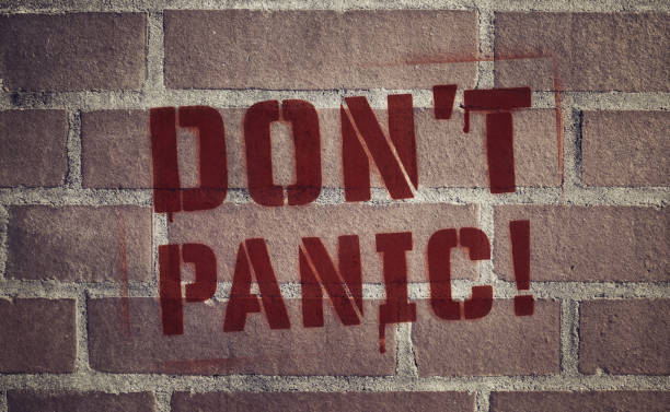 """Don't Panic!"" Stencil Spray-Painted on Brick Wall stock photo"