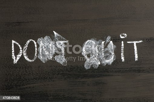Don't Quit transformed in Do It  message isolated on black background. Chalk drawing on blackboard. Business Concept image.