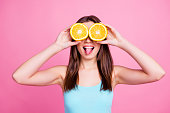 I don't see you! Portrait of amusing comic entertaining humorous laughable beautiful lovely cute pretty joke girl fooling around playing with orange slices, isolated on pink background