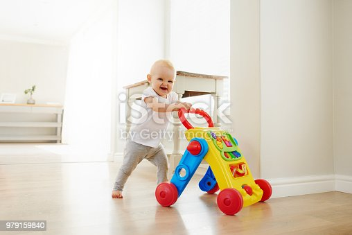 Portrait of an adorable baby girl playing with a toy walker at home