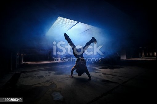 Silhouette of a young unrecognizable man dancing in an underground garage.