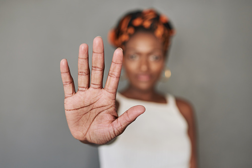 Studio portrait of a young woman holding her palm out against a grey background