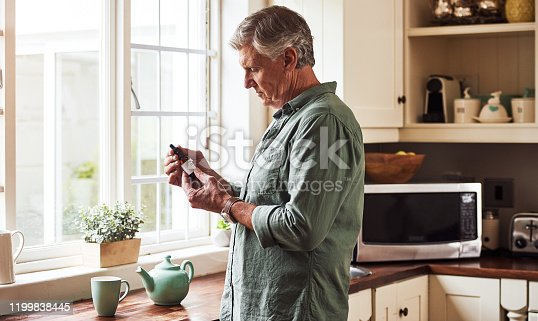 Cropped shot of a relaxed senior man preparing a cup of tea with CBD oil inside of it at home during the day
