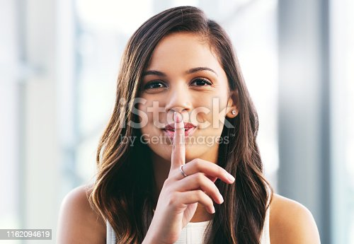 Portrait of a young businesswoman placing her finger on her lips in a modern office