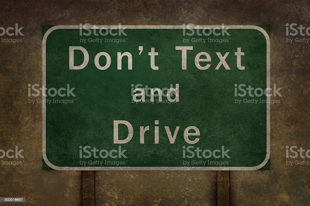 Don't Text and Drive road sign with ominous distressed treatment stock photo