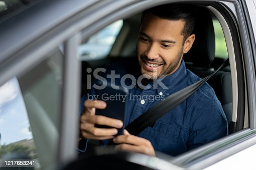 Portrait of a happy man texting and driving in his car on his cell phone – lifestyle concepts