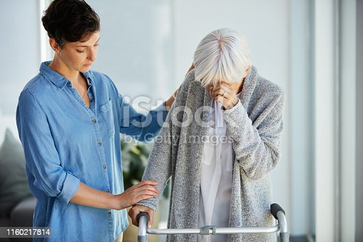 Cropped shot of an affectionate young woman consoling her upset aged mother while assisting her to use a walker
