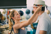 Happy young couple are exploring Queen Victoria Market in Australia. The woman has found a childs summer hat and is trying to squeeze it on her boyfriends head, as he pulls a face.