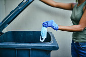 Cropped shot of an unrecognizable woman disposing of a used mask outdoors at home