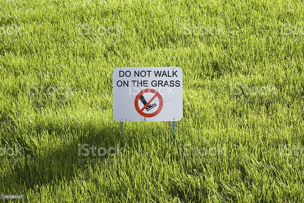 Don't walk on the grass stock photo