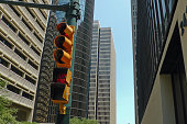 Traffic lights on red showing don't walk sign amongst modern buildings