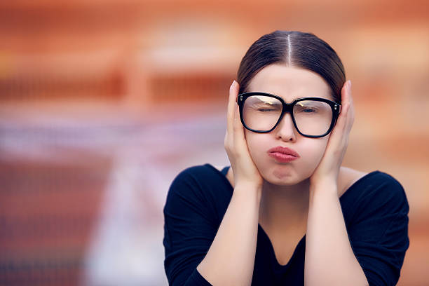don't wanna hear portrait of angry and sullen student with her hands covering ears, having a negative expression. hands covering ears stock pictures, royalty-free photos & images