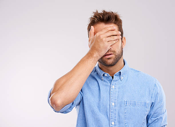 I don't wanna see this Studio shot of a handsome young man covering his eyes in regret against a gray background embarrassment stock pictures, royalty-free photos & images