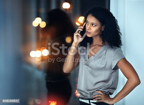 Shot of a young businesswoman talking on a mobile phone during a late night at work