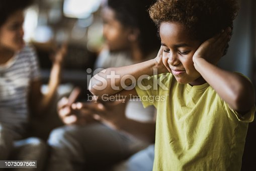 Small African American girl covering her ears while refusing to listen her parents arguing.