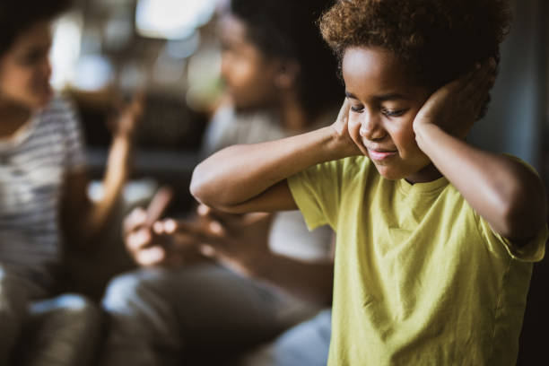 I don't want to listen my parents arguing! Small African American girl covering her ears while refusing to listen her parents arguing. hands covering ears stock pictures, royalty-free photos & images