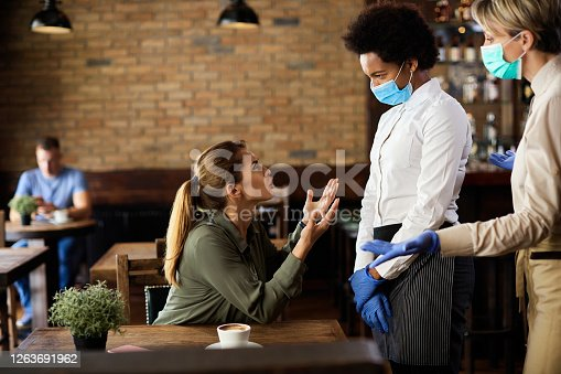 Displeased woman doesn't want to wear protective face mask and arguing with waitresses in a cafe during coronavirus epidemic.