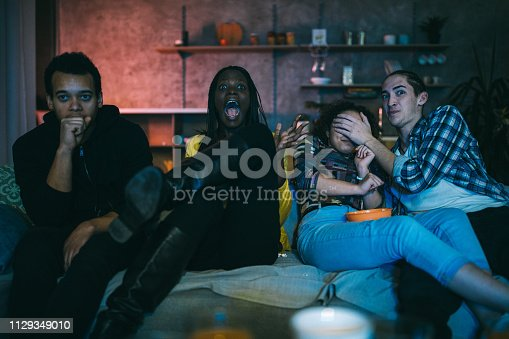 Young friends watching horror movie on TV at home, eating popcorn and chips at night