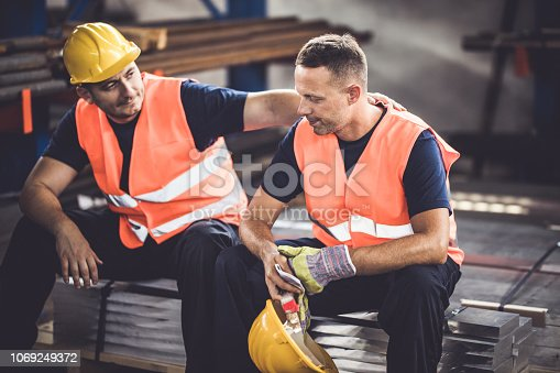 Sad manual worker being consoled by his colleague in aluminum mill.