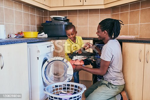Cropped shot of an adorable little boy assisting his dad with doing laundry at home